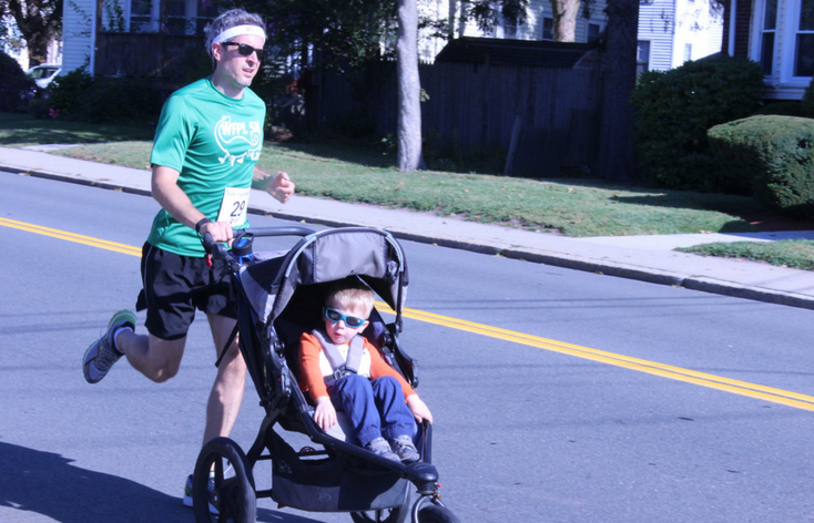 Man running in a road race while pushing a child in a stroller