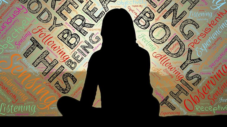 A woman sitting with mindfulness-related words surrounding her.