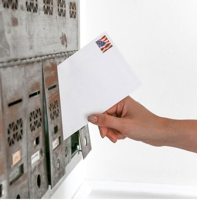 Hand putting a stamped letter into a mailbox.