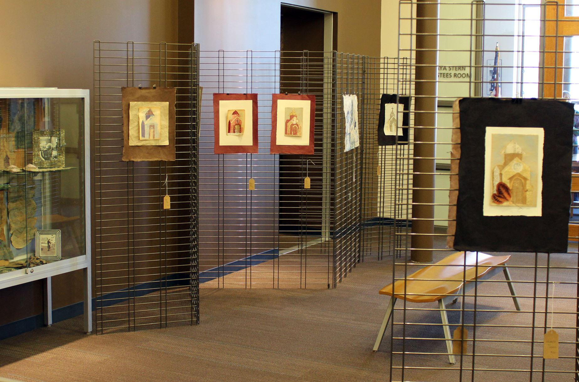 Art gallery with hanging drawings and display case
