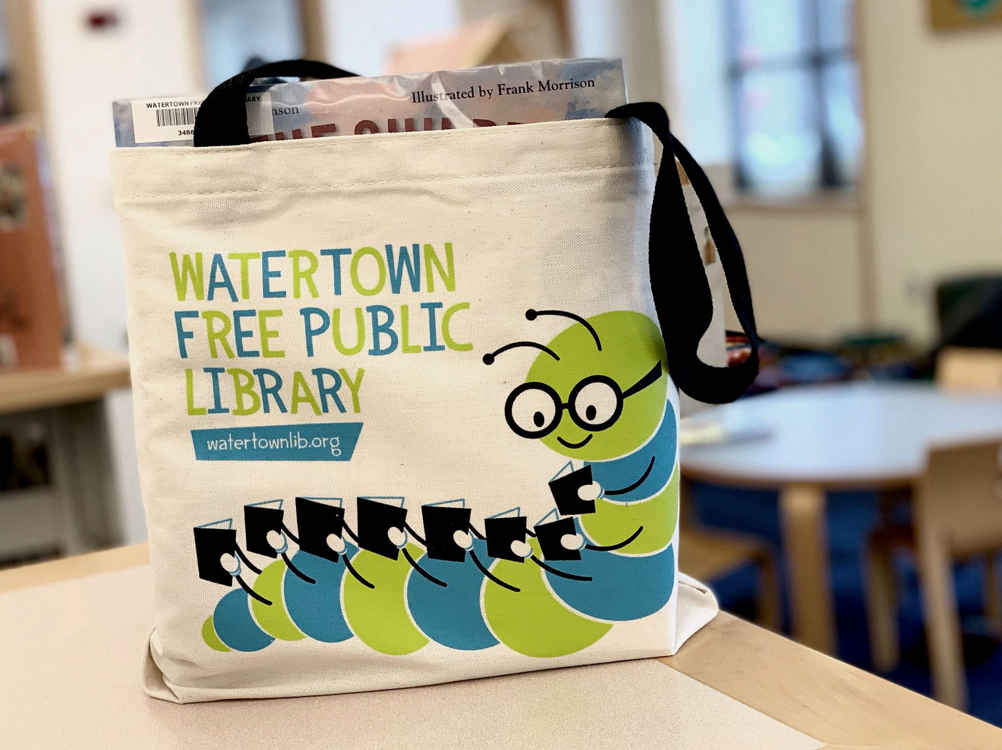 Image of a book bag with a graphic of a caterpillar reading.