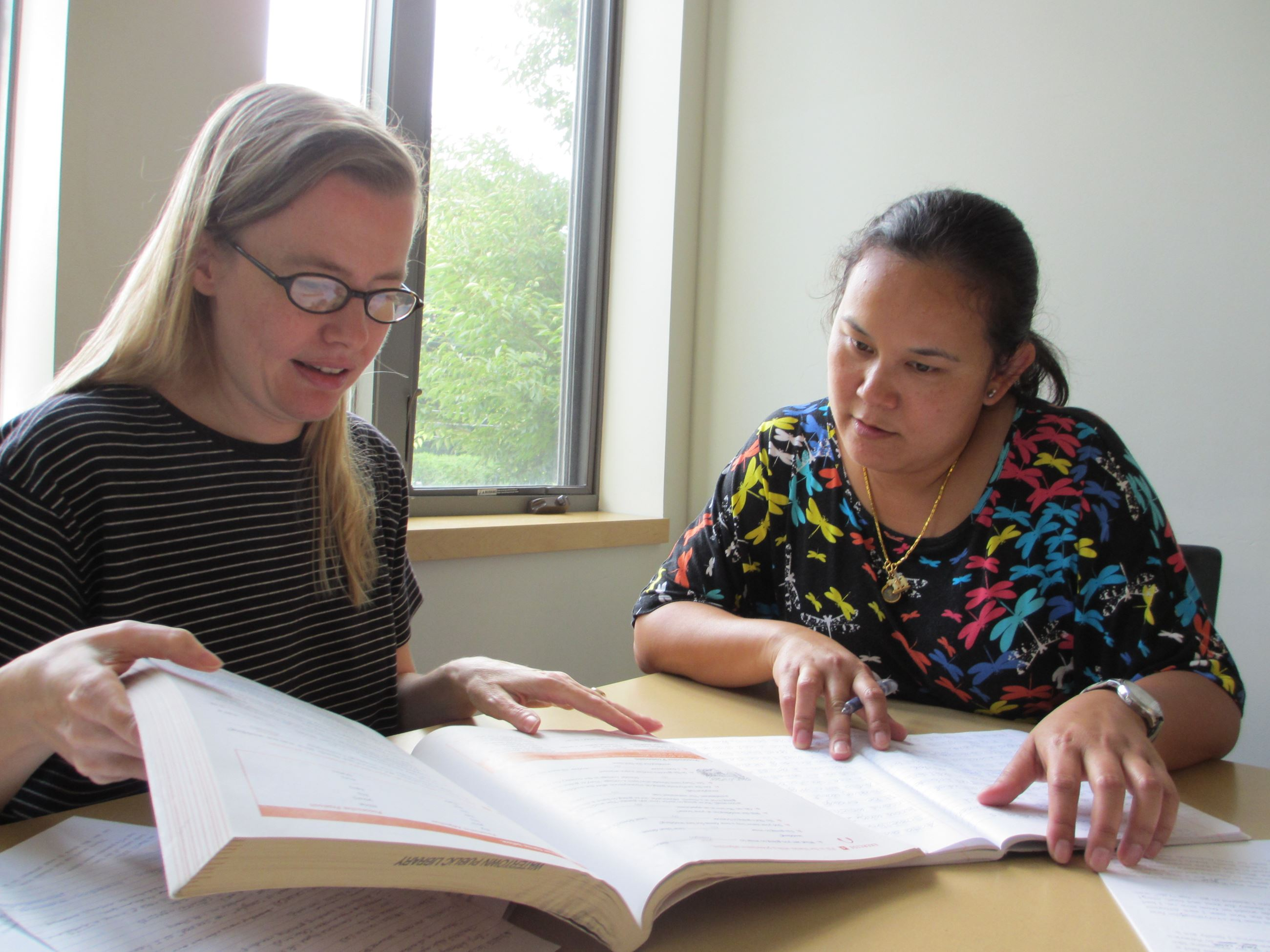Project Literacy tutor and student looking at a textbook together